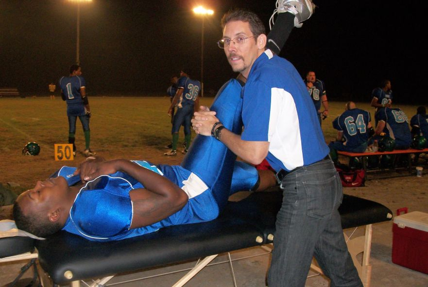 Dr. Austin performing a hamstrings muscle stretch on one of his semi-pro Springfield Foxes players.