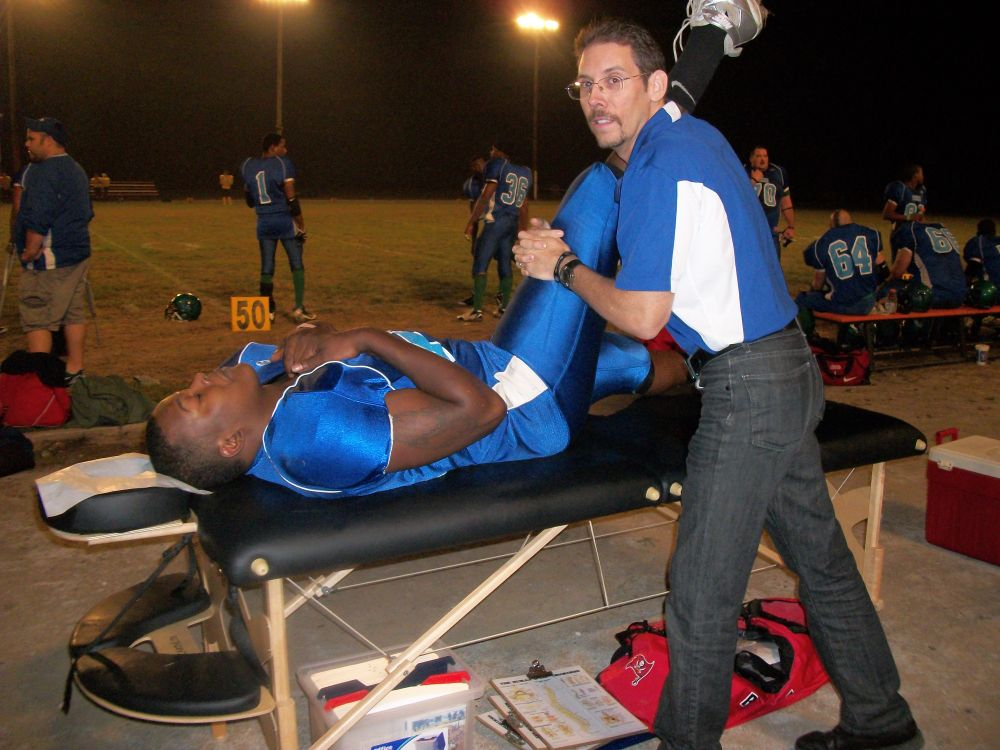 Dr. Todd Austin performs a hamstring stretch for a Foxes player