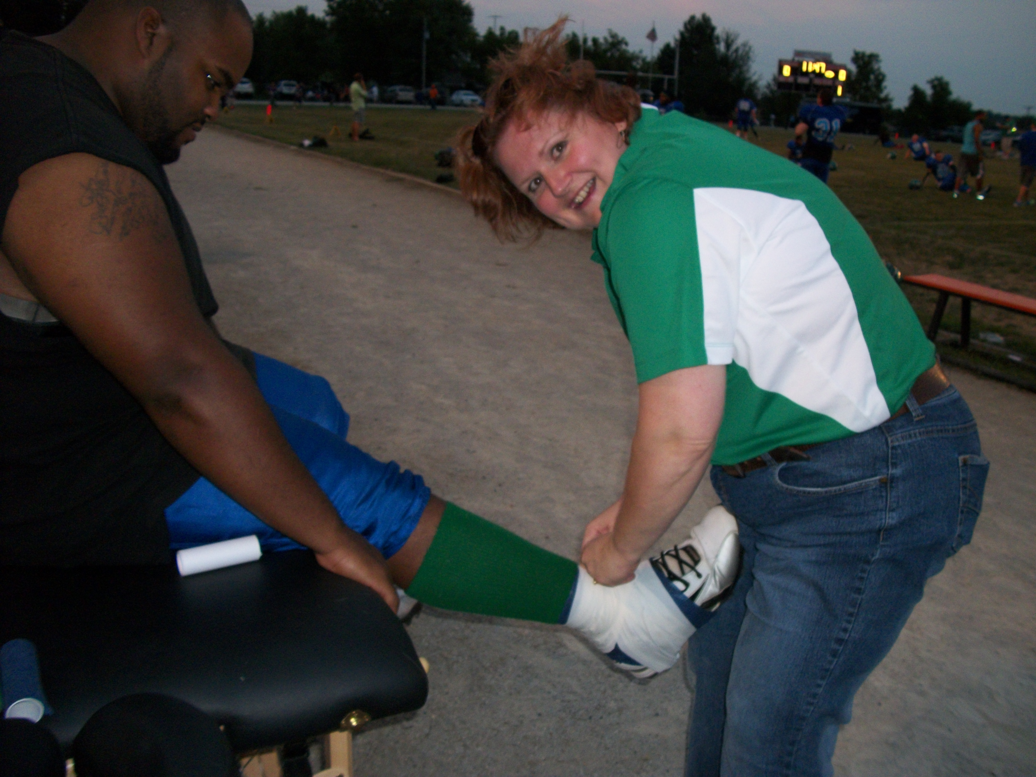 Assistant Trainer Eugena Austin, LMT tapes a player's ankle on the Foxes sideline.