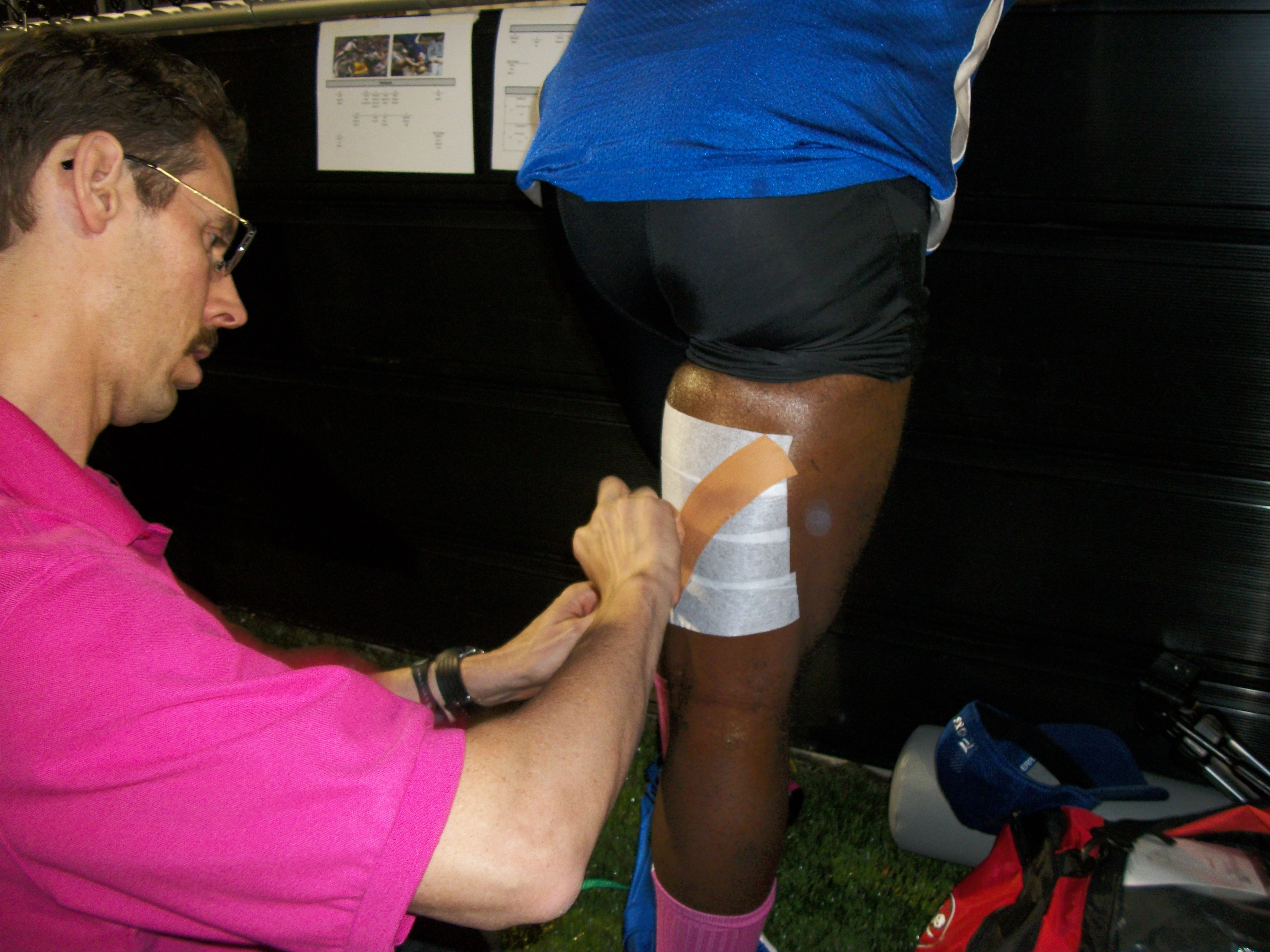 Dr. Todd Austin leukotaping #1 Gary Miller for a pulled hammy during the 1st half.